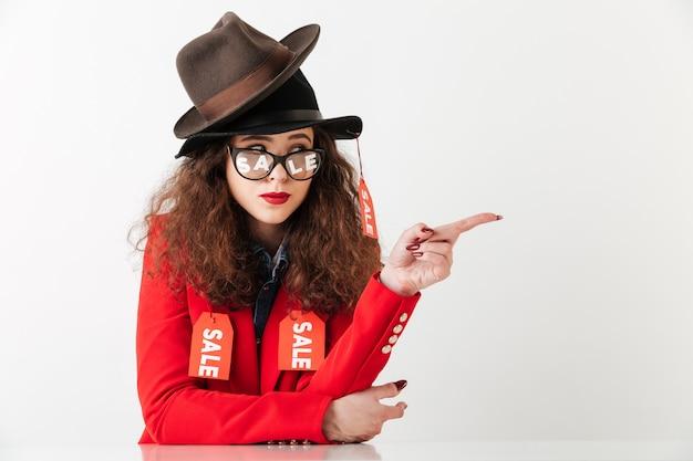 Moderne junge shopaholic frau, die kleidung mit verkaufsetiketten trägt