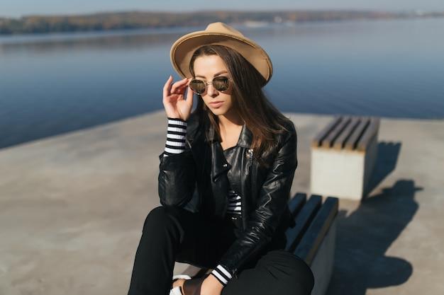 Moderne junge vorbildliche mädchenfrau sitzen auf einer bank im herbsttag am seeufer