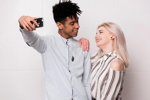 Moderne junge zwischen verschiedenen rassen lächelnde paare, die selfie auf smartphone nehmen