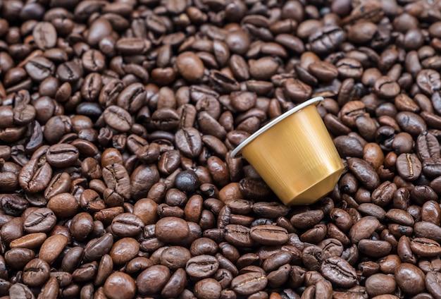 Moderne kaffeekapsel auf der röstkaffeebohne.