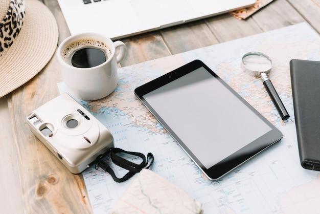 Moderne kamera; kaffeetasse; digitale tablette und lupe auf der karte