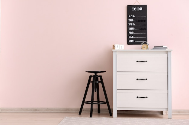 Moderne kommode mit hocker nahe farbwand im büro