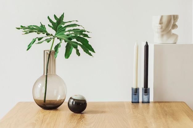 Moderne komposition des wohnzimmers mit holztisch, tropischem blatt in vase, kerzenständer, dekoration und eleganten persönlichen accessoires. vorlage.