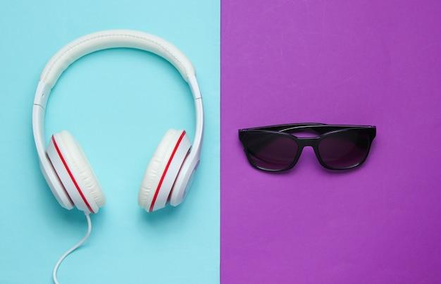 Moderne kopfhörer mit sonnenbrille auf farbigem hintergrund. kreatives musikkonzept. retro-stil.