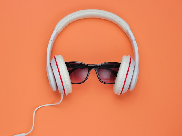 Moderne kopfhörer mit sonnenbrille auf korallenfarbenem hintergrund. kreatives musikkonzept. retro-stil.