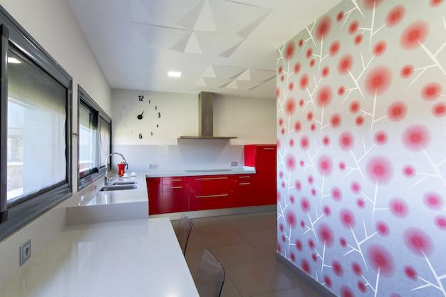 Moderne küche in rot mit außenansicht. innenarchitektur des hauses.