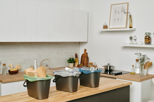Moderne küche mit geschirr und einer gruppe von plastikmülleimern