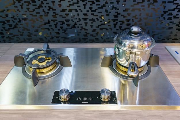 Moderne küchenmöbel mit dunstabzugshaube, schwarzem induktionsherd und backofen im haus