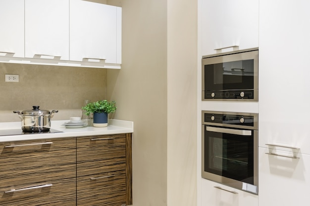 Moderne küchenmöbel mit zeitgemäßen küchenutensilien wie dunstabzugshaube, schwarzer induktionsherd