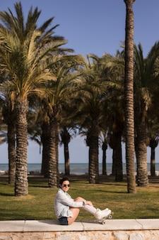 Moderne lächelnde attraktive junge frau, die nahe dem strand sitzt