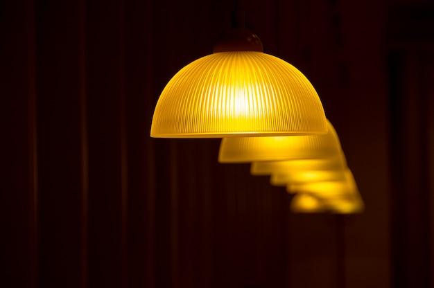 Moderne lampen, die von der decke auf einem dunklen hintergrund hängen