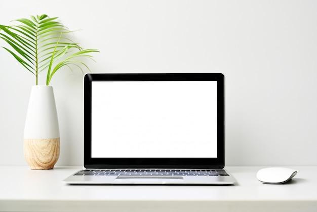 Moderne laptop-computer des leeren bildschirms mit maus auf hölzerner tabelle im büro