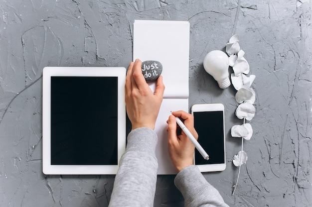 Moderne laptop, handy, tablette, kaffeetasse und notebook auf einem grauen hintergrund