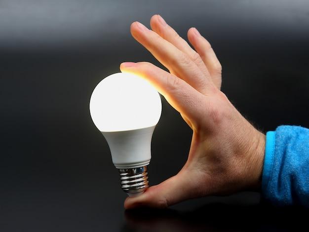 Moderne led-lampe ist eingeschaltet. enthaltenes led-licht in der handfläche einer person in einer dunkelheit. elektroindustrie