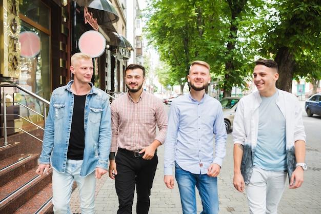 Moderne männliche freunde, die zusammen auf stadtstraße gehen