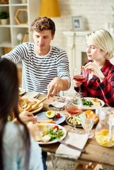 Moderne menschen, die mit freunden zu hause speisen