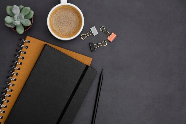 Moderne, minimalistische tischplatte mit notizbüchern, kaffeetasse, grüne saftige anlage über dunklem strukturiertem hintergrund. büro- oder geschäftsarbeitsplatz mit kopienraum für text. kreative flachlage.