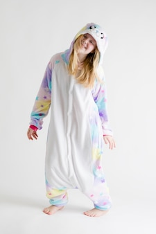 Moderne mode - schönes blondes mädchen, das auf einem weißen hintergrund in den kigurumi-pyjamas, häschenkostüm aufwirft