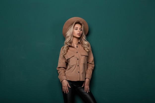 Moderne modische frau mit langen blonden haaren in einem beige eleganten hut in einem vintage-hemd in stilvollen lederhosen im retro-stil, der in einem studio nahe einer grünen wand aufwirft