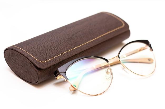 Moderne modische goldene damenbrille für das sehen und eine ledertasche auf hellem hintergrund.