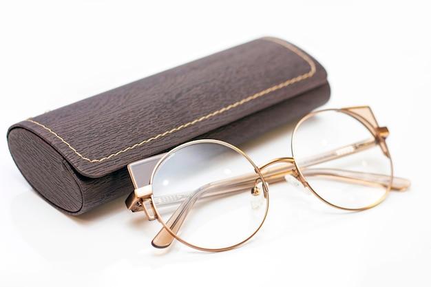 Moderne modische goldene damenbrille für sehkraft und ledertasche auf heller oberfläche.