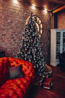 Moderne modische rote ledercouch mit kissen. beschnittener weihnachtsbaum. ziegelwand. loft-design.