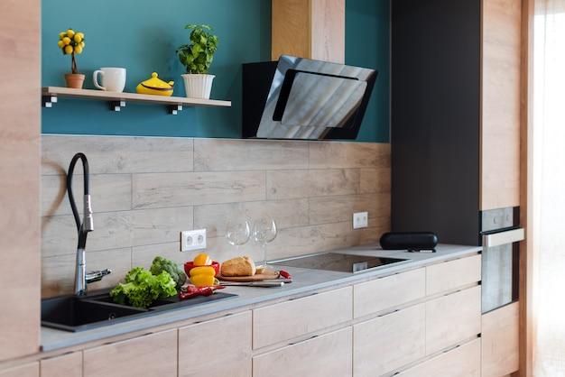Moderne möbel in luxusküche. minimalistisches skandinavisches interieur in loft-wohnung mit holzmöbeln, lampen, betonelementen und pflanzen.