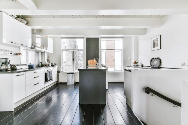 Moderne möblierte küche mit schwarzem boden und weißen schränken im haus mit weißen holzbalkendecken und großen fenstern
