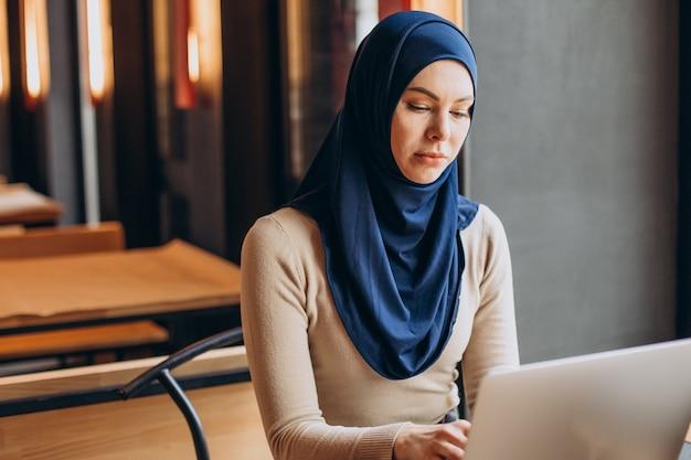Moderne muslimische frau, die in einem café am laptop arbeitet
