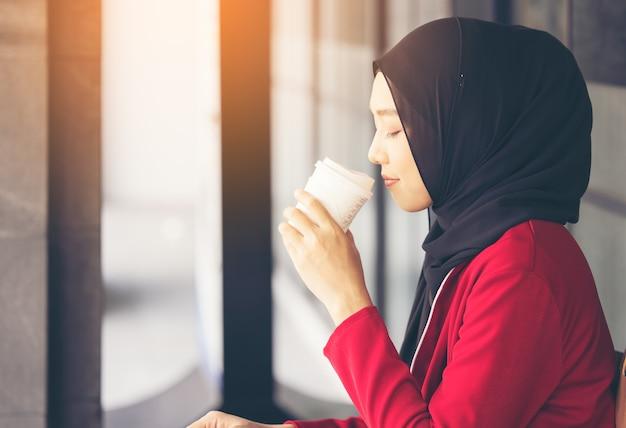 Moderne muslimische frau, die über die straße mit einem kaffee zum mitnehmen geht