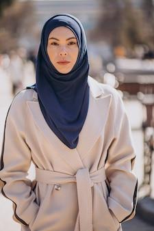 Moderne muslimische frau mit kopftuch, die auf die straße geht