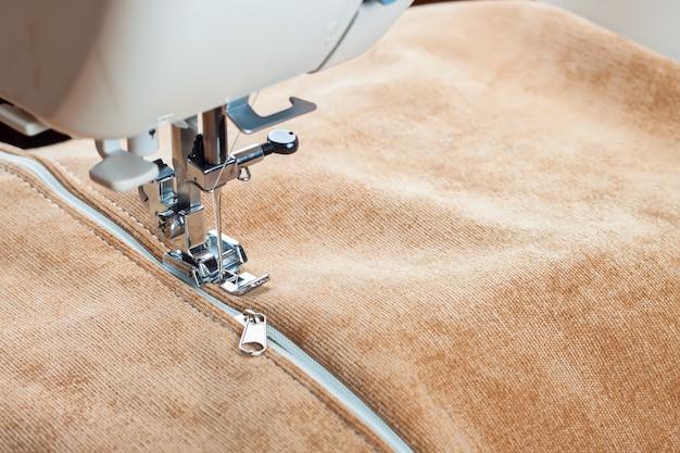 Moderne nähmaschine näht auf dem reißverschluss auf biege kleidungsstück. nähvorgang