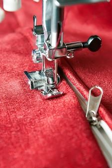 Moderne nähmaschine näht auf dem reißverschluss auf rotem kleidungsstück. nähvorgang