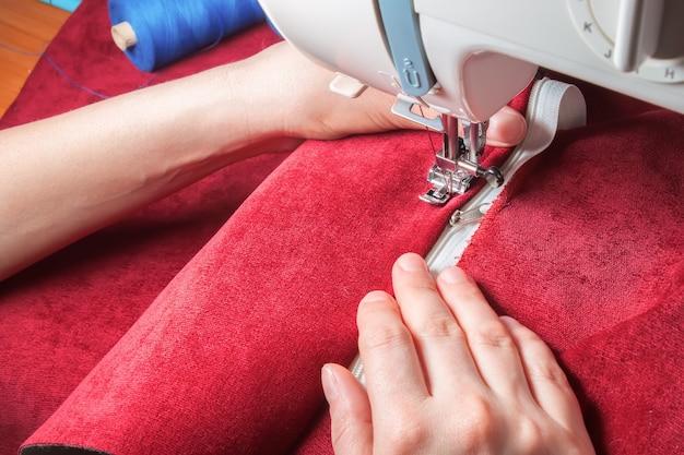 Moderne nähmaschine näht den reißverschluss an rotem kleidungsstück an. nähvorgang