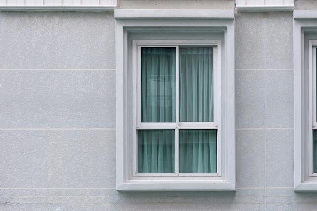 Moderne neue wohngebäudefenster mit vorhang-uv-schutz im inneren. außenansicht.