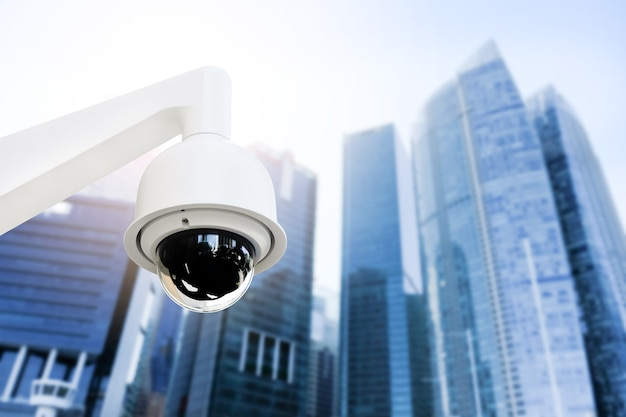 Moderne öffentliche cctv-kamera auf strommast mit unscharfem gebäudehintergrund und kopierraum.