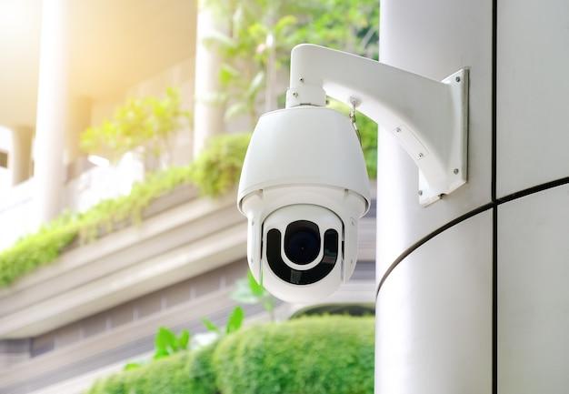 Moderne öffentliche cctv-kamera mit unscharfem gebäudehintergrund und kopierraum.