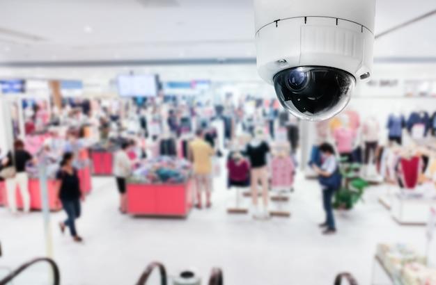 Moderne öffentliche cctv-kamera mit unscharfem inneneinkaufshintergrundhintergrund und kopienraum.