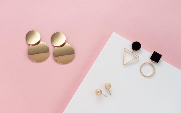 Moderne ohrstecker auf weißen und rosa farben wand