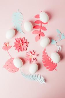 Moderne ostern-dekoridee - weiße eier und origamipapier crakt blumen und pläne auf rosa