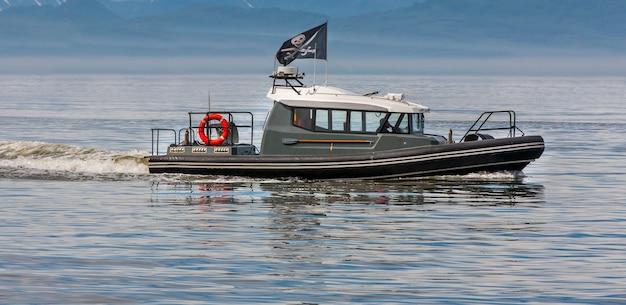 Moderne piraten auf einem motorboot in einer bucht unter piratenflagge