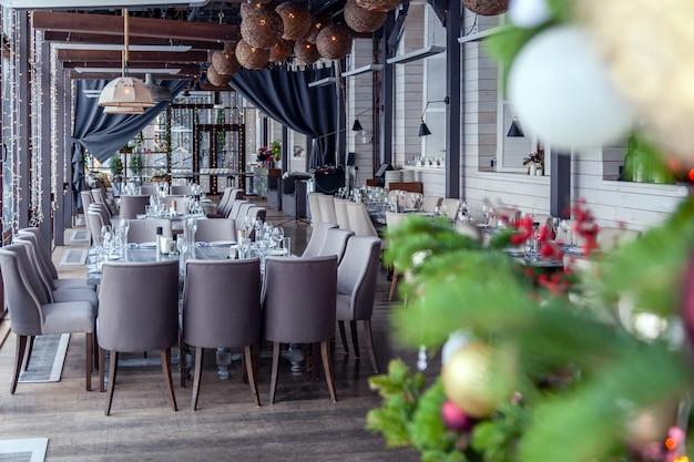 Moderne restauranteinstellung der weihnachtsinnenveranda des neuen jahres, bankett dienend.