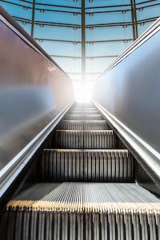 Moderne rolltreppe mit fenster im hintergrund.