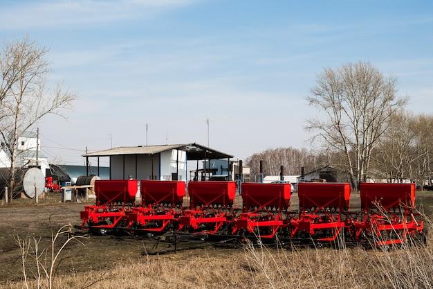 Moderne saatgutmaschine. landwirt traktorsaat. roter mähdrescherpflug. aussaat auf landwirtschaftlichen feldern im frühjahr.