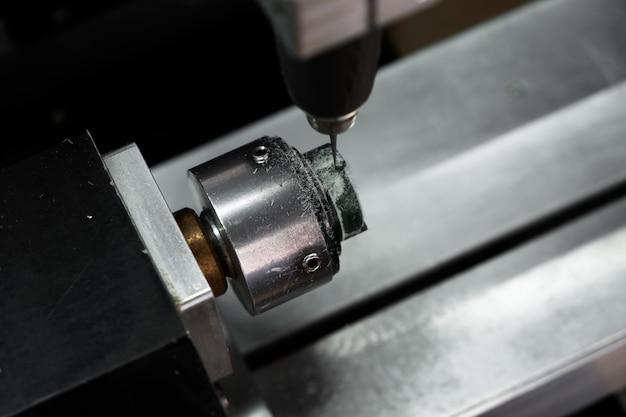 Moderne schmucktechnologie. cnc-maschine schneidet grünen wachsring aus. herstellung von ringen. basteln von schmuck.