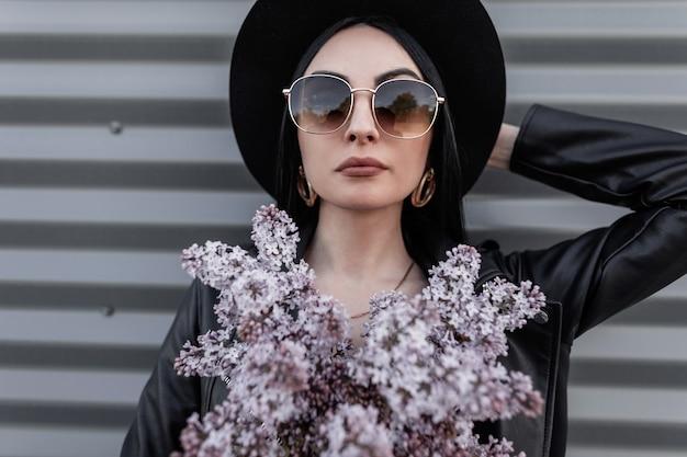 Moderne schöne frau in modischer sonnenbrille in vintage-hut in stilvoller lederjacke mit blumenstrauß in lila farbe, die in der nähe des metallgebäudes in der stadt posiert. attraktive mädchenmode geht durch die stadt.