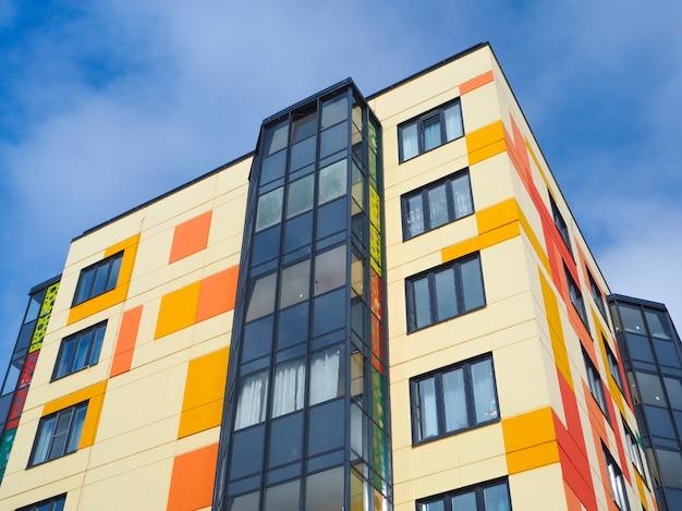 Moderne schöne neue gebäude. farbige wand auf dem hintergrund des blauen himmels