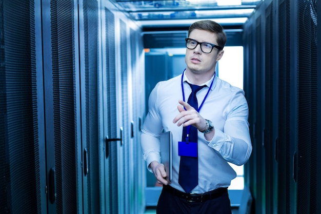 Moderne schränke. entschlossener professioneller bediener, der einen laptop hält und nach dem richtigen serverschrank sucht