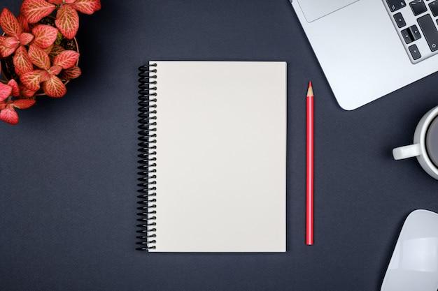 Moderne schreibtischtabelle mit laptop und leerer notizbuchseite