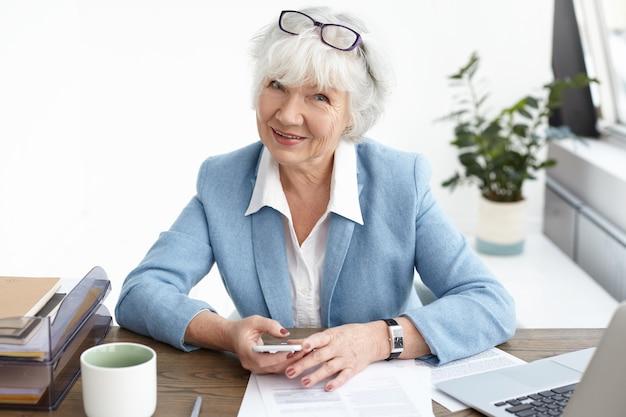 Moderne, selbstbewusste frau mittleren alters in den sechzigern, die eine kleine pause macht, an ihrem arbeitsplatz sitzt, nachrichten überprüft oder soziale medien über das handy scrollt, kaffee trinkt und mit einem lächeln schaut